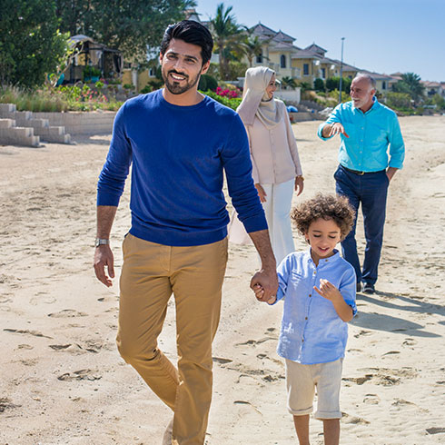 a family, a dad, wife, son and grandfather walk along a beach