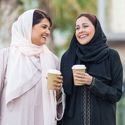 two women walk drinking coffee and laughing