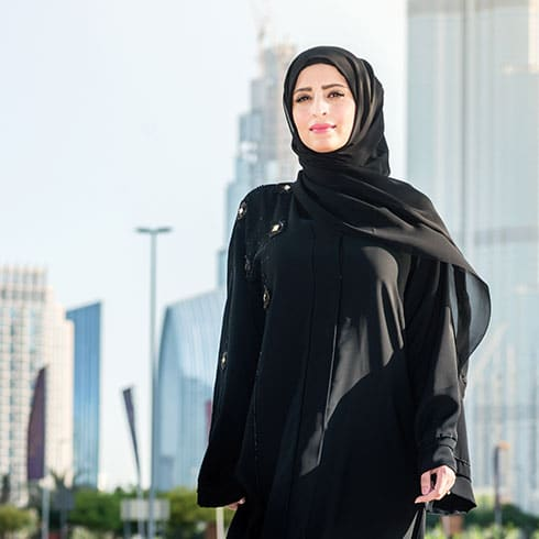 a woman in a hijab stands in a city