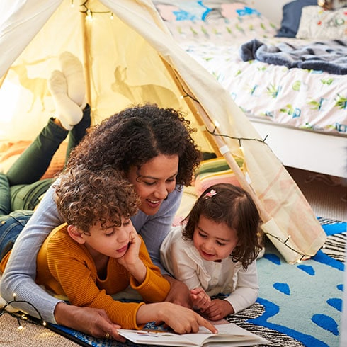 a woman and two children sit in a tent indoors reading a book