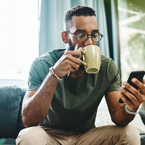 a man sits drinking from a mug looking at his phone