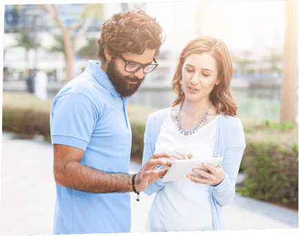 two people stand outside looking at a tablet